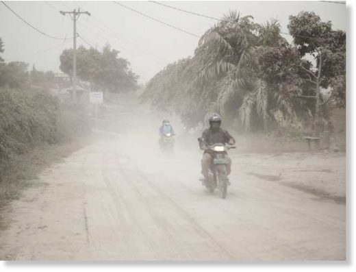 Motorists ride on a road covered in volcanic ash