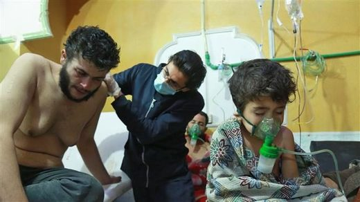 Syrian children and adults receive treatment for a suspected chemical attack at a makeshift clinic
