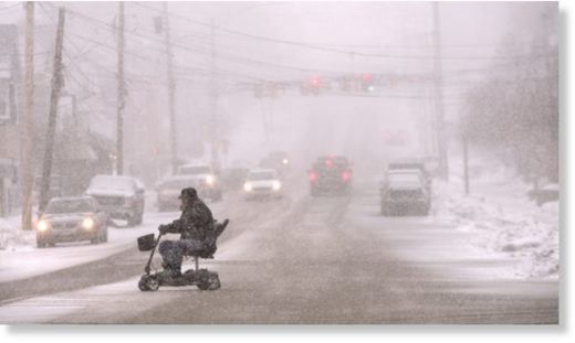 A man rides an electric wheel chair on Union Street as heavy snow started falling in Bangor Tuesday afternoon.