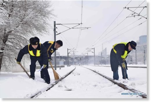 Workers remove snow from train tracks at Shenyang North Railway Station in Shenyang, northeast China's Liaoning province, March 15, 2018.