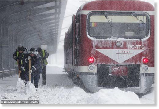Municipal workers clear ice and snow from the platforms of the Gara de Nord, the main railway station in Bucharest, Romania, Friday, March 23, 2018.