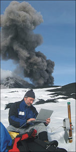 Volcanologist Marco Neri during the winter of 2008-2009 downloads data onto a laptop from the ERN1 radon sensor at the site (later buried in lava) known as the Tower of the Philosopher. Behind him, less than 1 kilometer away, ash billows fro