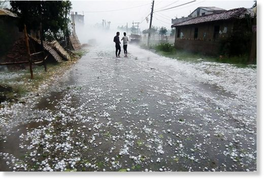 Two men stand on the road to see the hailstones fallen in Pipara area of Durga Bhagawati Rural Municipality, in Rautahat district, on Friday, March 30, 2018.