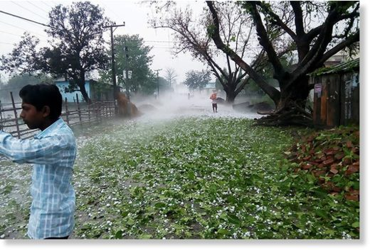 A man takes pictures of hailstones fallen in Matsari area of Durga Bhagawati Rural Municipality, in Rautahat district, on Friday, March 30, 2018.