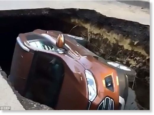 Incredible footage from the scene shows the stricken car lying on its side in the sinkhole
