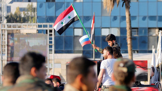 A Syrian soldier waves Russian and Syrian flags during a protest against air strikes in Damascus,Syria April 14,2018