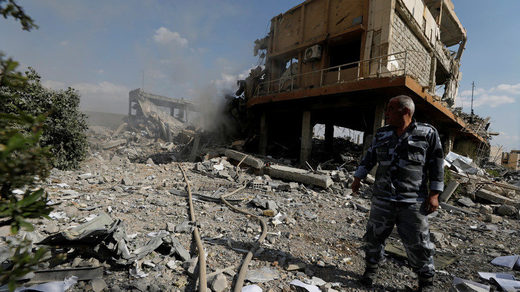 Syrian firefighter is seen inside the destroyed Scientific Research Centre in Damascus, Syria,