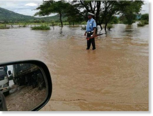 Police Constable Abdi Galgalo of Sultan Hamud Police Station captured by a motorist while directing traffic on a flooded section of the Nairobi-Mombasa highway at Sultan Hamud on Saturday.