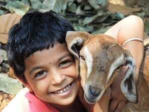 child with baby goat