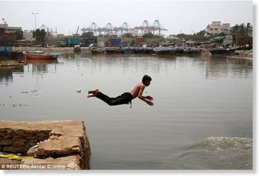A boy jumps into the water to cool off during hot and humid weather