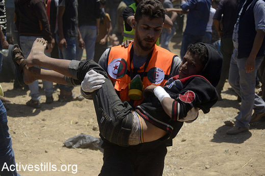 A medic carries a Palestinian child during a protest in the Gaza Strip