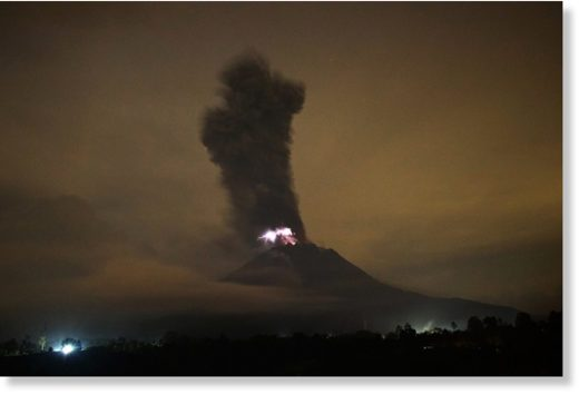 This picture taken on May 20, 2018 shows the Mount Sinabung volcano spewing ash into the air and lightning from its crater in Karo.