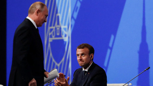 Russian President Vladimir Putin is applauded by his French counterpat Emmanuel Macron after delivering a speech during a session of the St. Petersburg International Economic Forum (SPIEF), Russia May 25, 2018.