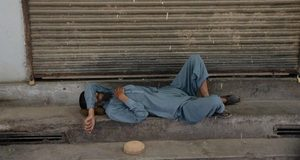 An Afghan Muslim man sleep in front of a shop