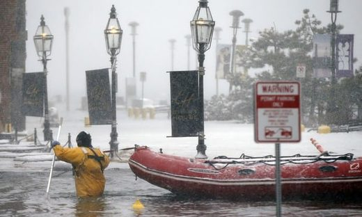 A firefighter wades through waters from Boston Harbor