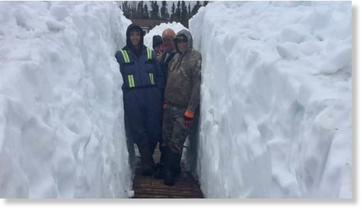 Staff at Igloo Lake Lodge stand amid six-foot-tall snowbanks that encompass the Labrador fishing camp on June 13.
