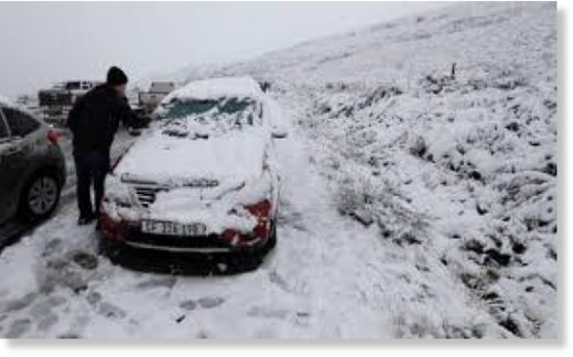 A motorist removes the snow from his car on the Swaarmoed Pass, 10 km outside Ceres in Western Province Cape, South Africa, on July 3, 2018.