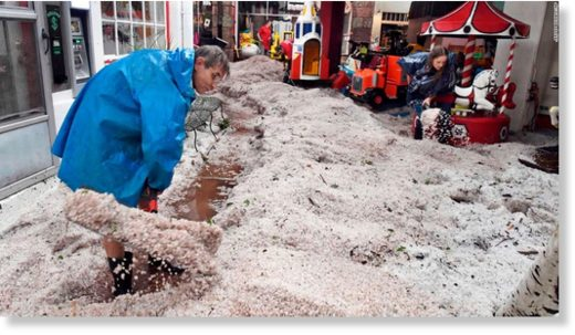 Ron Allen, an employee with the Manitou Springs Penny Arcade, and other employees dig out of hail drifts at the arcade in Manitou Springs, Colo., Monday, July 23, 2018. A storm dropped hail and caused flash flood and tornado warnings for the area.