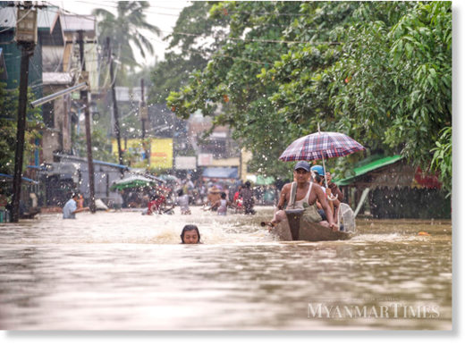 Residents make their way through flooded streets in Bago Region.