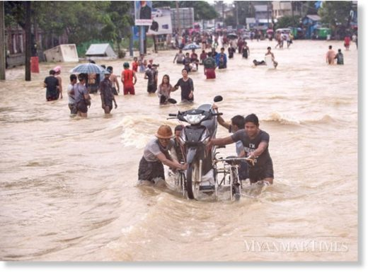 People in Bago Region wade through floodwater as they move to higher ground. The Department of Meteorology and Hydrology warns of more rain this week