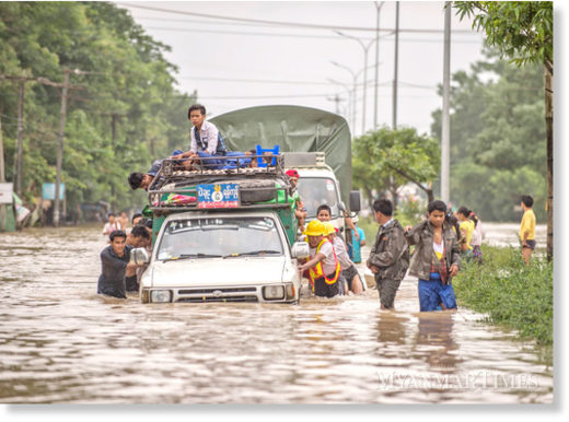 People help push a stalled truck in Bago on Saturday.