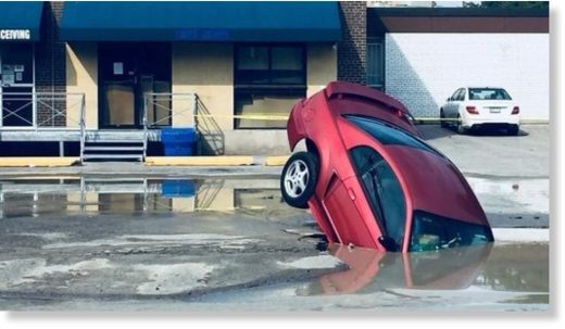 A car was partly swallowed by a sinkhole caused by a watermain break in Toronto's Weston neighbourhood on Aug. 7, 2018.