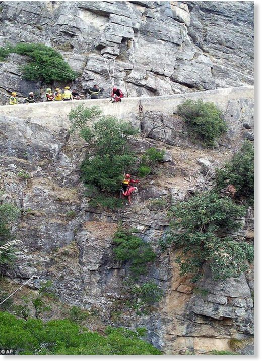 Rescuers work at the Raganello Gorge in Civita, Italy today: TV images show rescuers scaling down the side of a steep rock face to bring hikers to safety