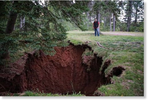 Mark Rushton stands near a large sinkhole that developed in the Oxford Lions Park.