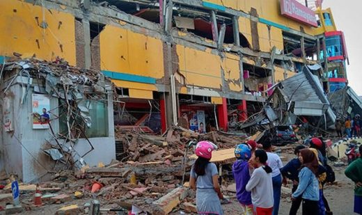 Residents outside a badly damaged shopping mall following Friday's tsunami in Palu