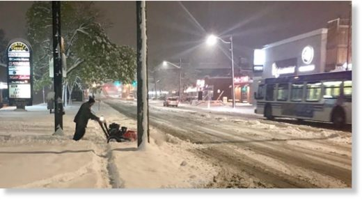 A man clears snow from a section of sidewalk along 14th Street S.W. early Tuesday morning.