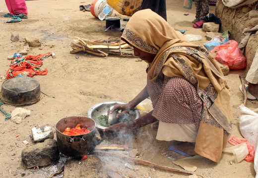 A displaced Yemeni woman from Hodeida cooks food outside a shelter