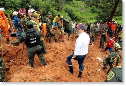 Governor of Santander Didier Tavera (centre), stands next to rescue workers as they work at the area where nine people died by mudslides caused by heavy rains, according to local authorities, in Barrancabermeja, Colombia on Sunday.