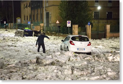 A man tries to reach a car that has been blocked by ice after a severe hailstorm hit Rome, Italy, on Sunday evening