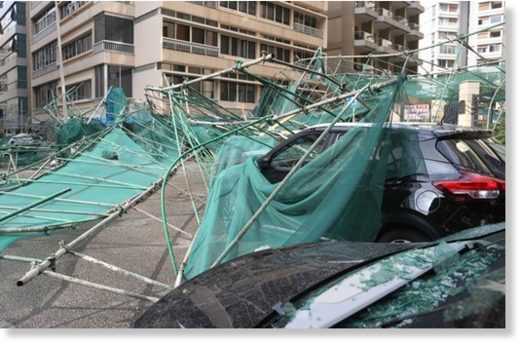 Cars are damaged after a scaffold falls over from the wind, in Raoucheh