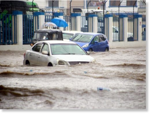 Motorists wade through a flooded road at railways roundabout in Mombasa county yesterday after a heavy downpour.