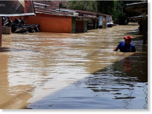 A resident wades through floodwater in Padangbulan district in Medan, North Sumatra, on Sept. 16.