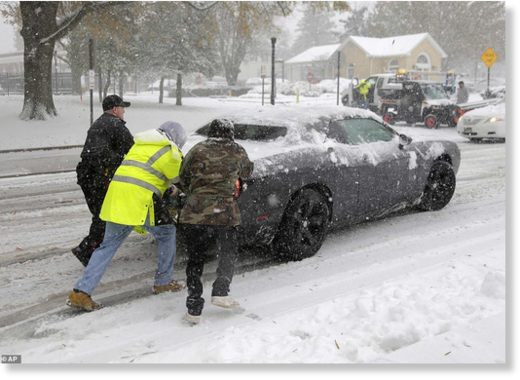 A police officer and others help push a car t