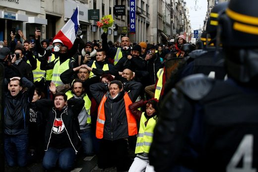 Demonstrators kneel in front of French CRS riot police in Paris