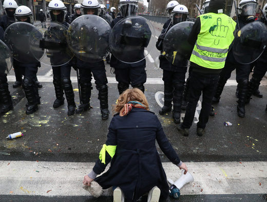 A woman kneels in front of police blocking the street during the