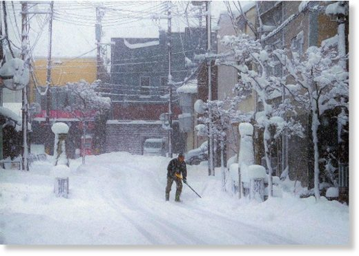 A man shovels snow in the city of Yokote,