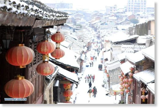 Tourists roam on a snow-covered ancient street