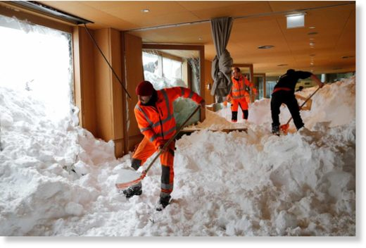 Workers shovel snow out of a restaurant after