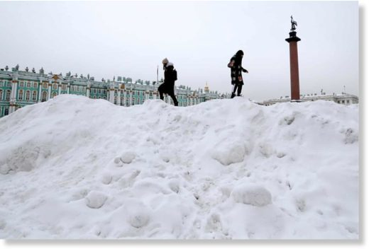 Girls climb piles of snow in Dvortsovaya (Palace) Square near the Winter Palace after a heavy snowfall in St Petersburg, Russia