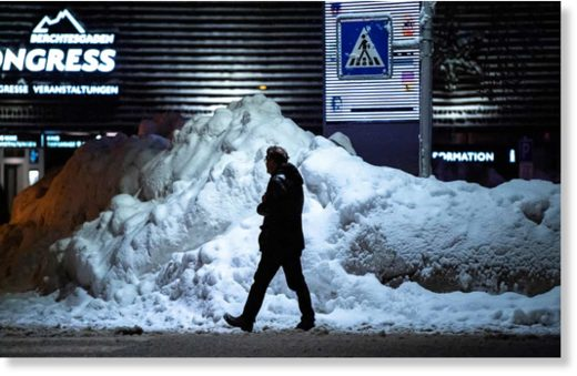 A man walks past a pile of snow in the town centre of Berchtesgaden, Bavaria, Germany
