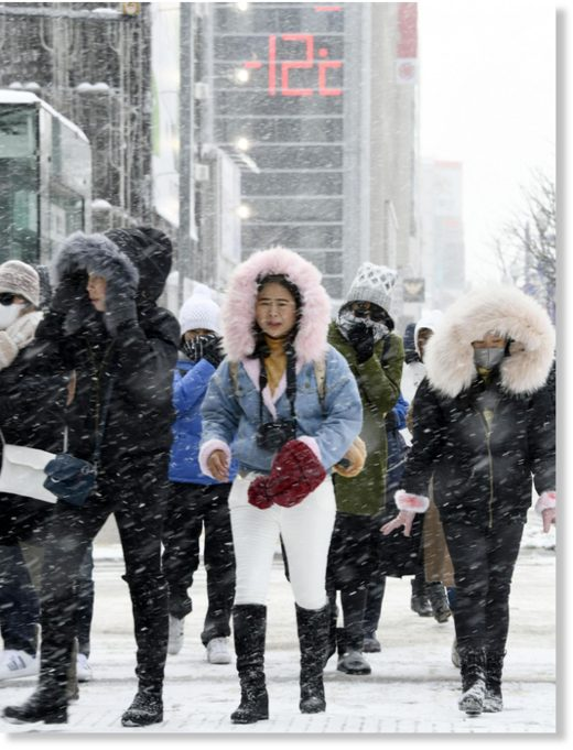 People walk in Sapporo on Friday as the