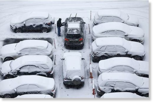 A man clears snow off his car during a snowfall in Moscow