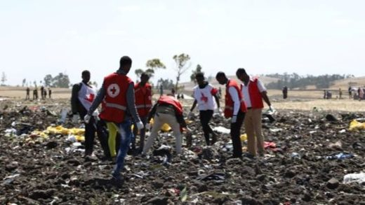 Emergency workers work amid debris at the crash site of Ethiopia Airlines
