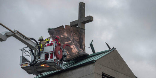 Firefighters in Frankfurt try to secure the tin roof of a church tower in the district of Gallus
