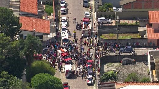 People gathered in front of Raul Brasil school, where students and teachers were killed