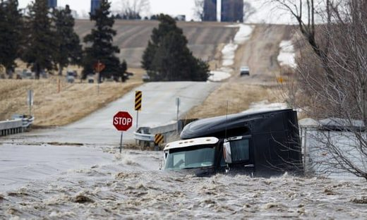 A semi truck and trailer are swept off the road by floodwaters in Arlington, Nebraska